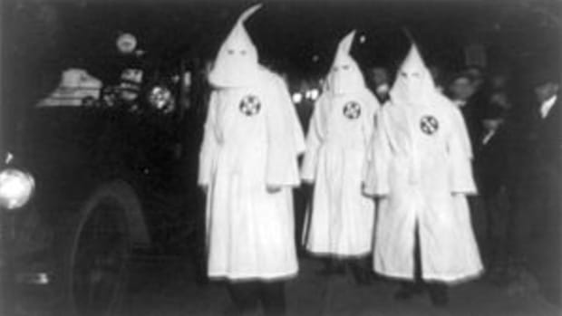 Three Ku Klux Klan members standing beside aut...