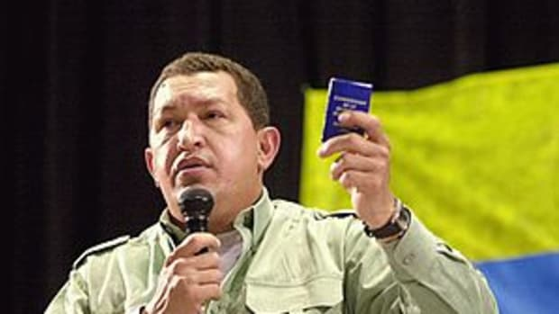 Chávez holds a miniature copy of the 1999 Vene...