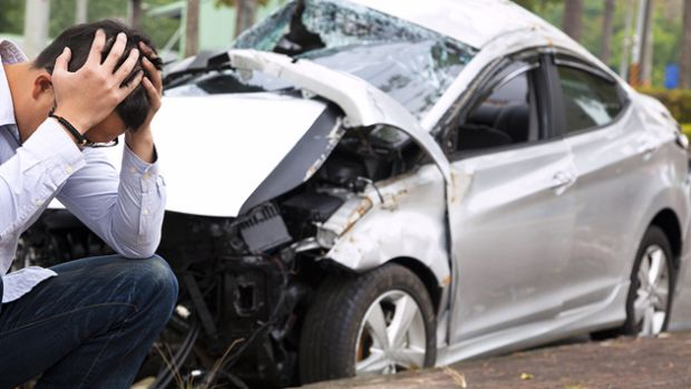 white-car-totaled-man-crouched-by-tree-mst