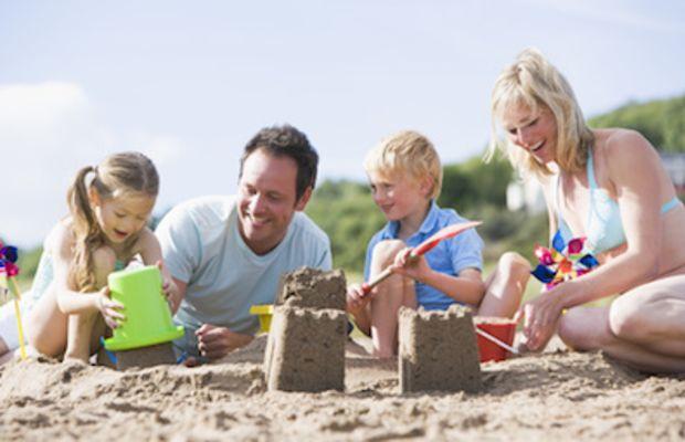Family on beach making sand castles smi