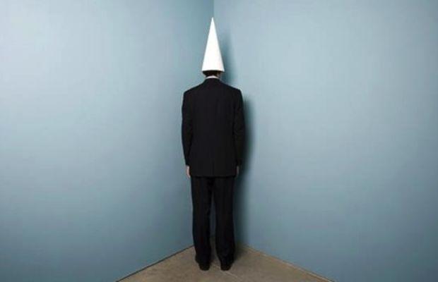 Businessman_wearing_dunce_cap_standing_