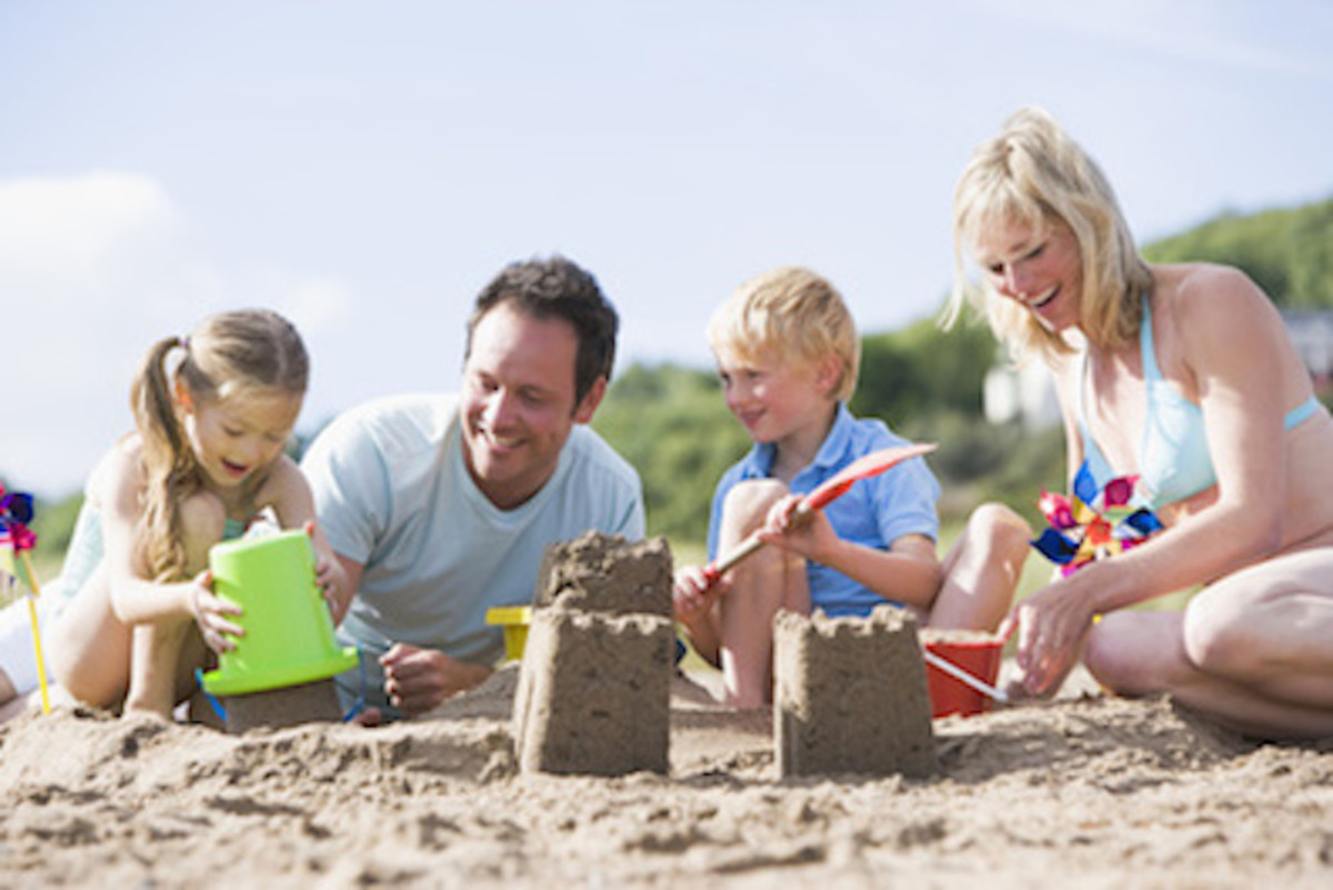 Family on beach making sand castles smi