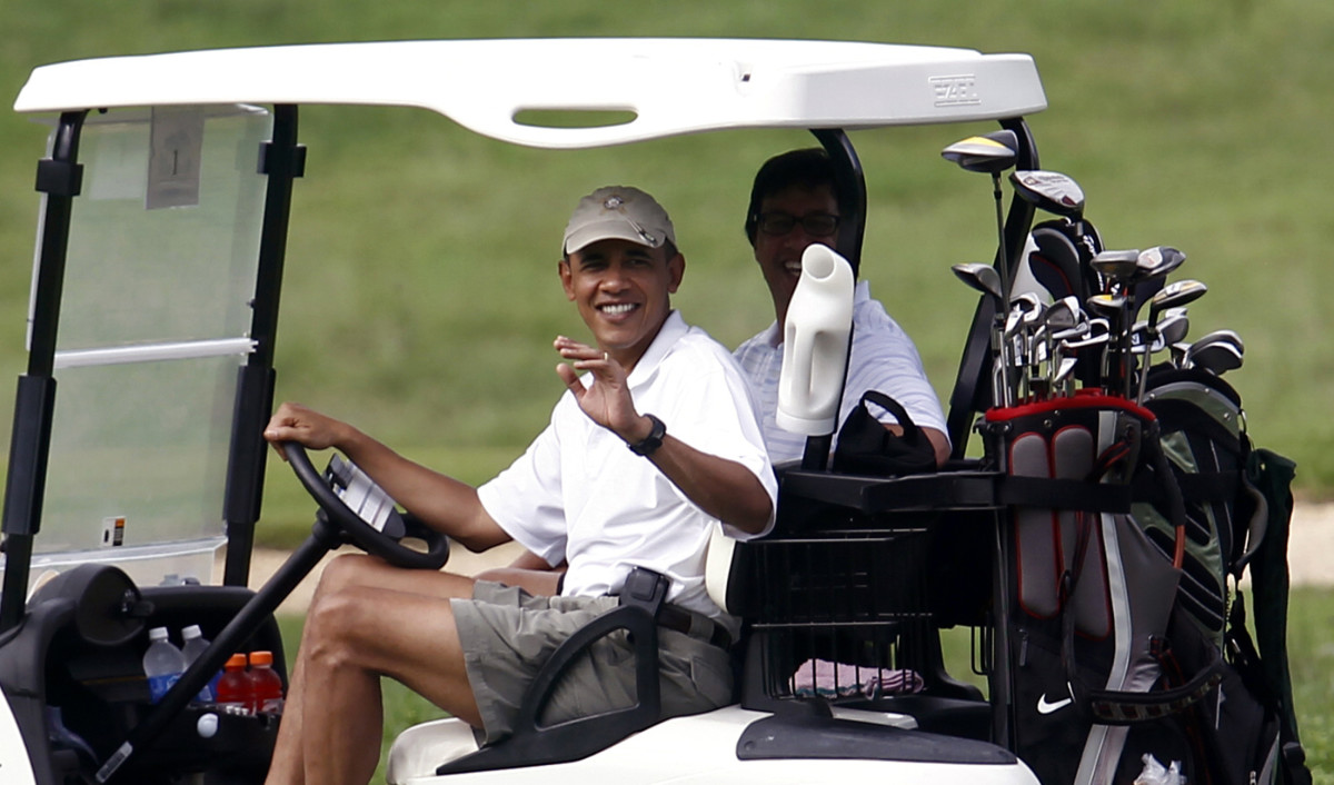 US President Obama waves from a golf ca