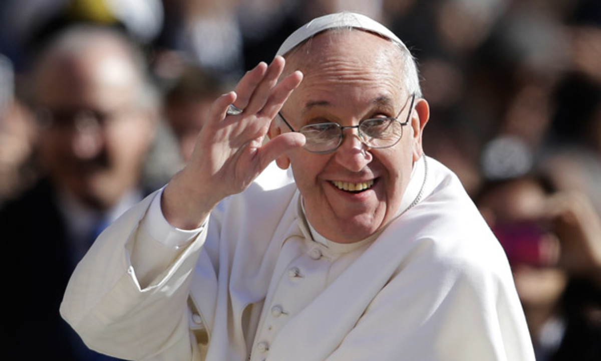 Pope Francis waves to crowds as he arri