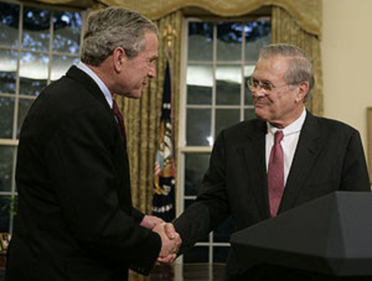 President George W. Bush shakes the hand of ou...